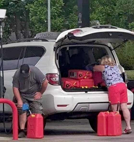 hoarding gasoline a couple are filling 5 gallon cans of gas
