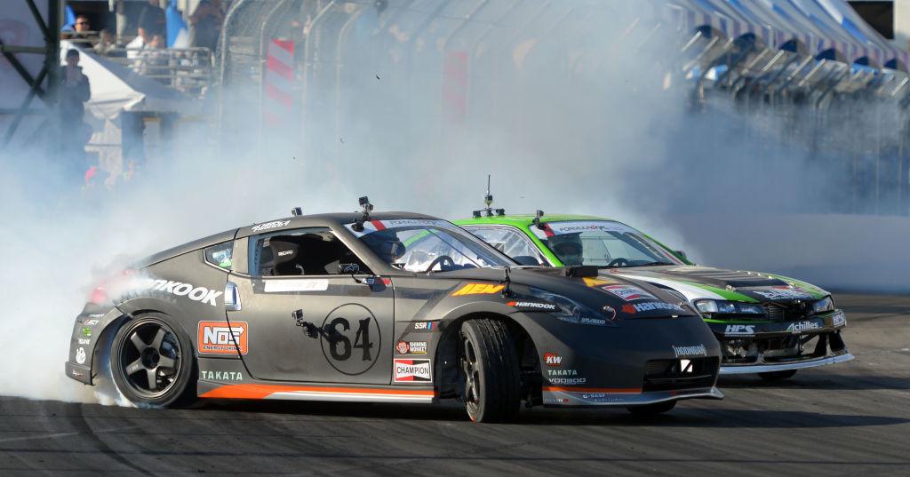 Two Formula Drift cars slide out of a corner spewing smoke