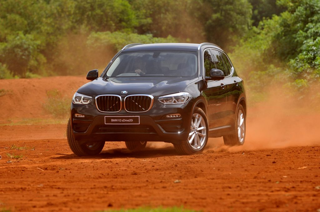 a BMW X3 luxury subcompact SUV variant driving off-road in red sand.