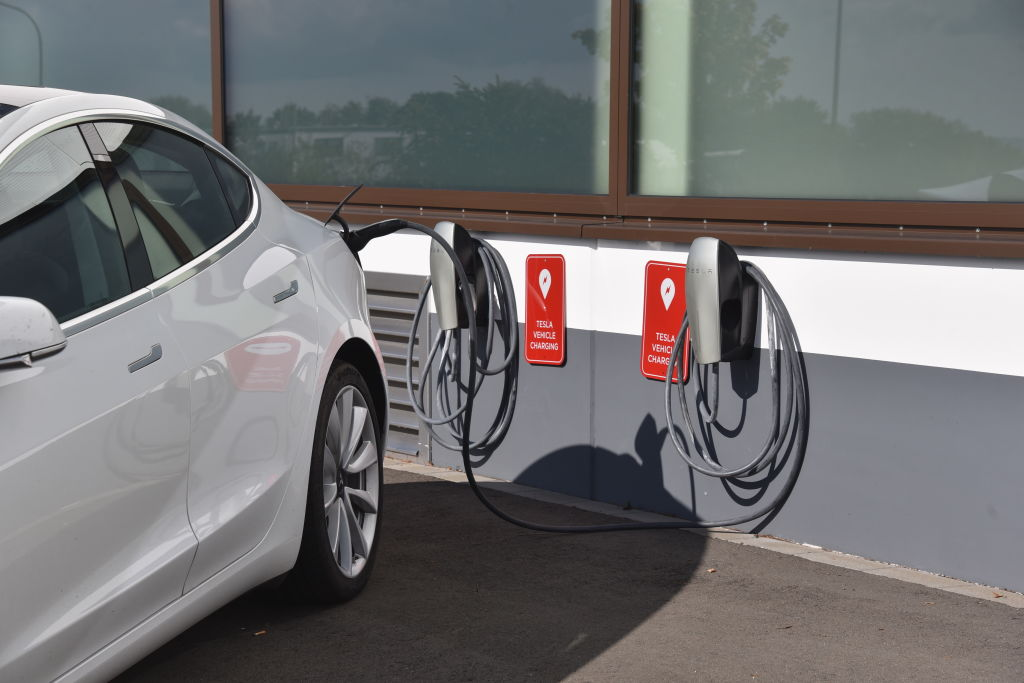 A white Tesla Model Y plugged into a charger outside