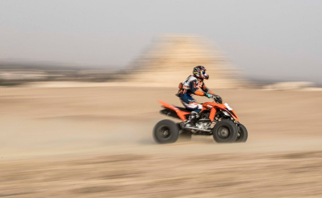 an ATV rider going fast on a quad in the desert
