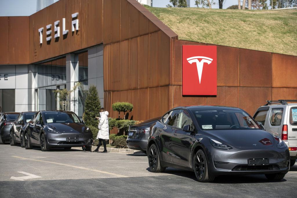 A grey Tesla Model Y sits outside a showroom