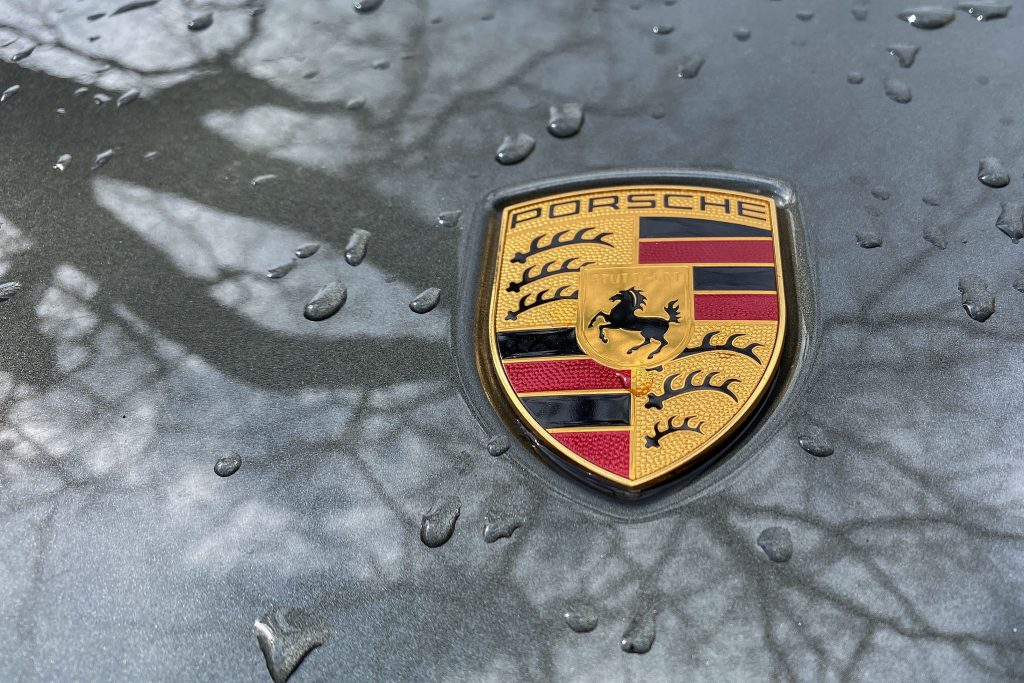 Porsche logo on a raindrop speckled car hood reflecting trees in the paint coat.