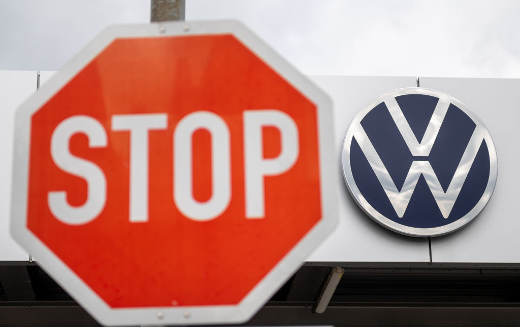 A stop sign in front of the Volkswagen logo on a white building