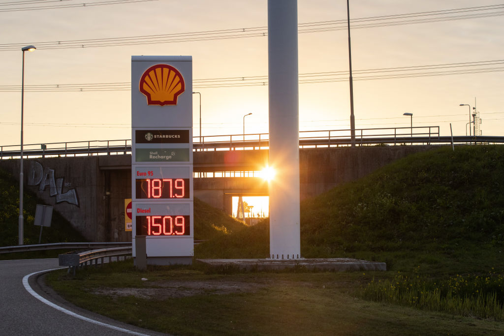 The sun sets over the highway behind a Shell gas station in Rotterdam
