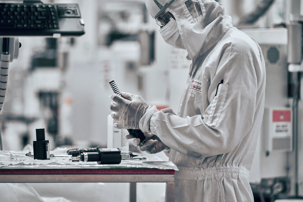 A man works in a lab, wearing protective garb while producing semiconductors.
