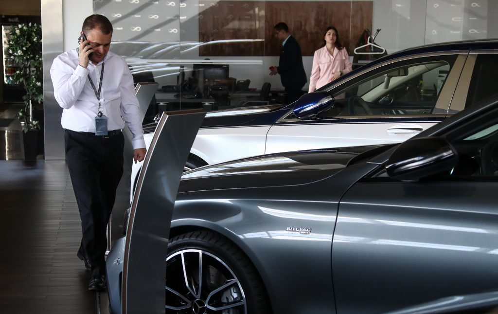 the interior showroom at a mercedes-benz car dealership while patrons are new car shopping