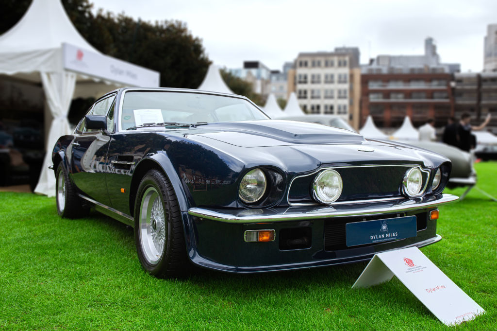 A dark blue 70s era Aston Martin V8 Vantage sits on a grass lawn