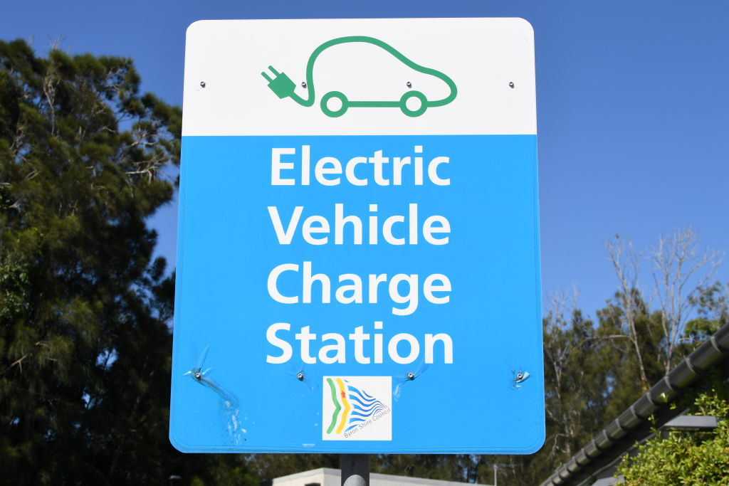 """A sign stating """"EV charge station"""" on a blue background"""