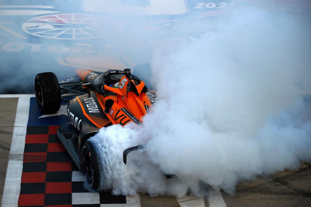 An orange Mclaren Arrow Indy Car does a burnout.