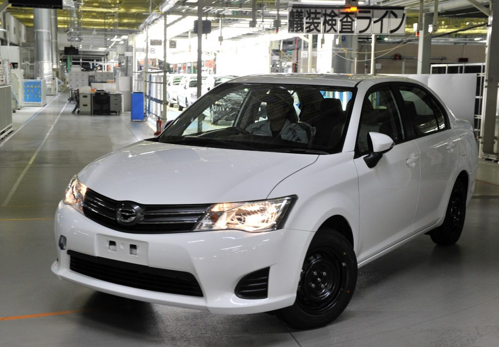 A white 2012 Toyota Corolla coming off the assembly line.