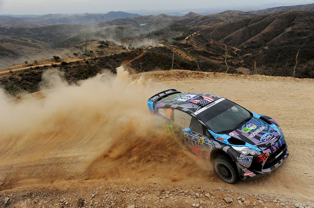Ken Block drifts his Ford WRC car on a dirt road in Mexico