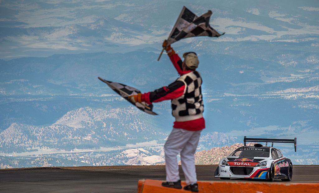 A white and black hill climb car with a huge wing, driven by Sebastian Loeb crosses the line at Pikes Peak.