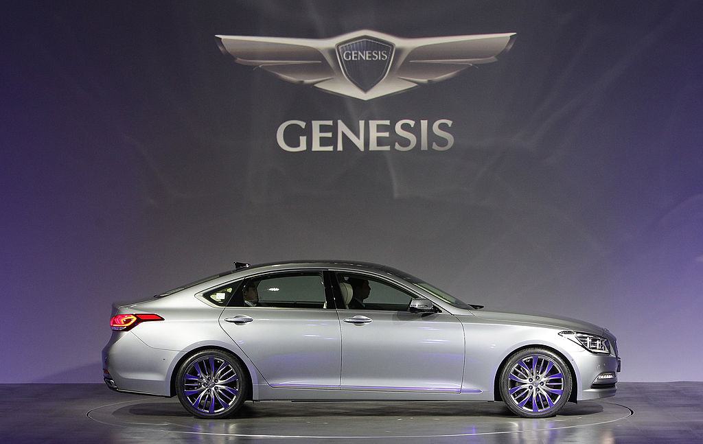 A silver Genesis sedan on stage with the Genesis logo in the background