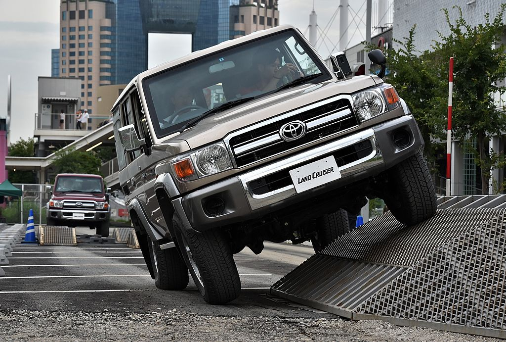 a 70 Series Land Cruiser generation SUV in a demo driving over an obstacle