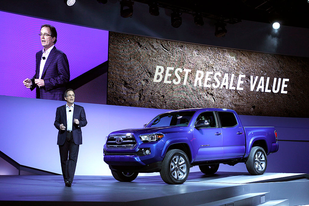 a blue Toyota Tacoma at an auto show on display with a best resale value banner in the background.