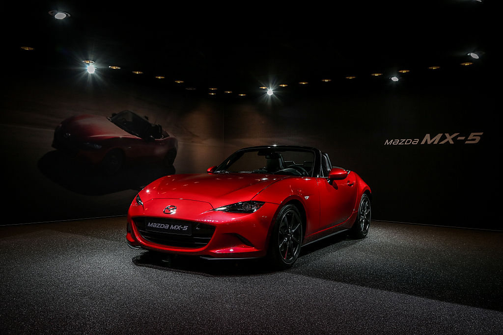 A red Mazda MX-5 on display under lights at its debut, photographed from the front 3/4