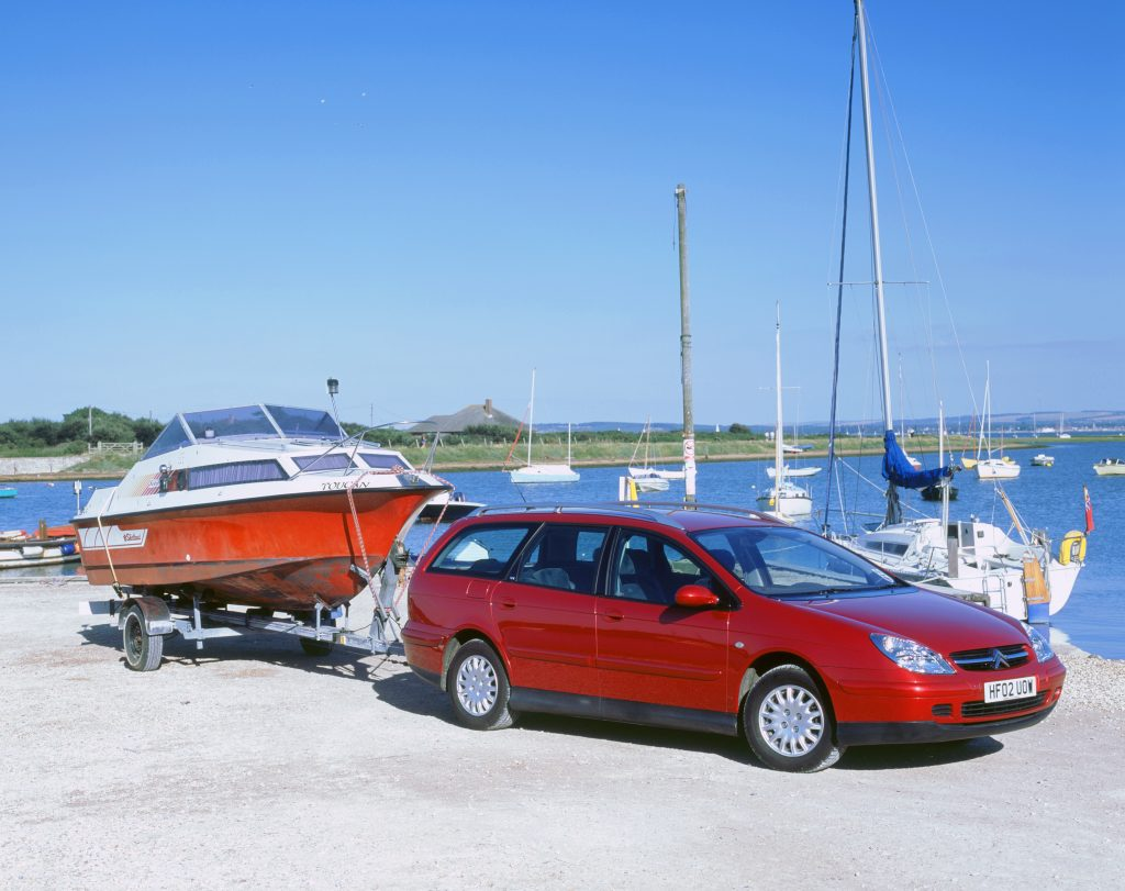 A red 2002 Citroen C5 hdi crossover towing a boat by a harbor