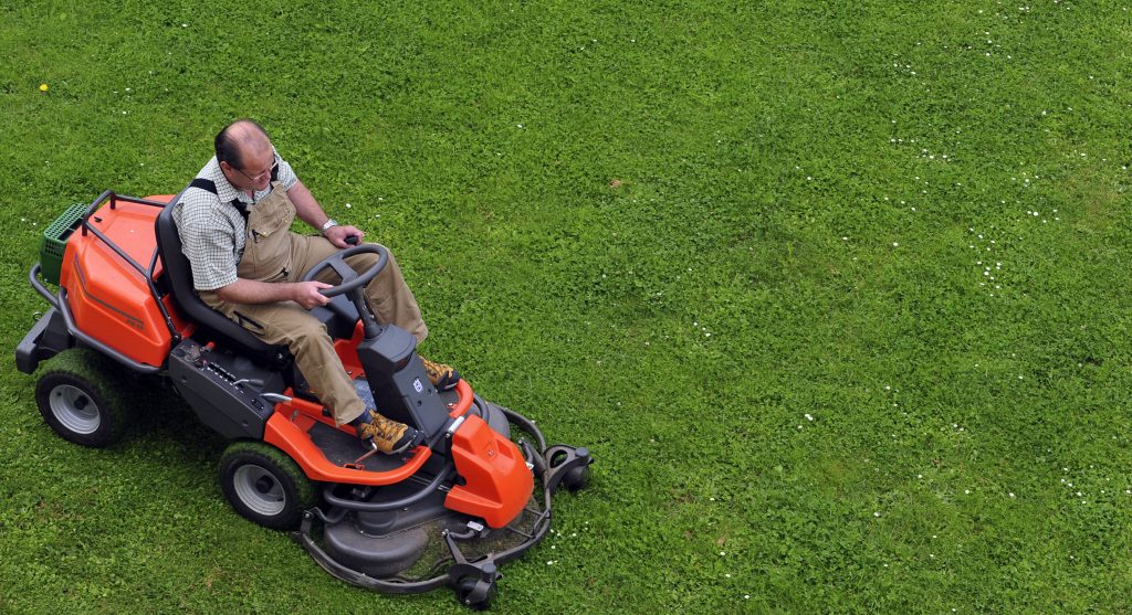 a man mowing a pristine lawn with a lawn tractor