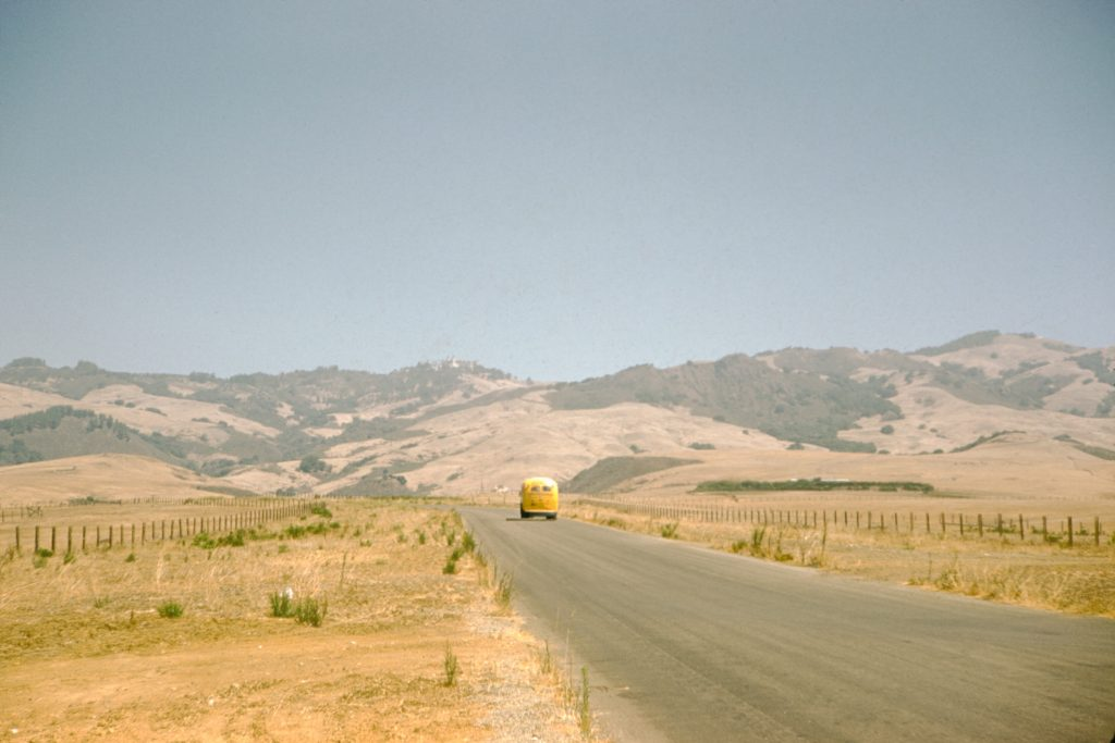 A yellow Volkswagen bus travels along a country road that cuts through a prairie covered in dry grass, low rolling hills can be seen in the background on a summer road trip