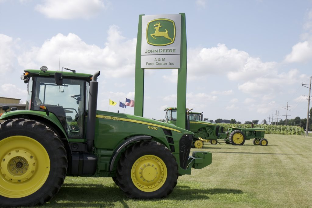 a John Deere tractor in front of a John Deere sign on a sunny day