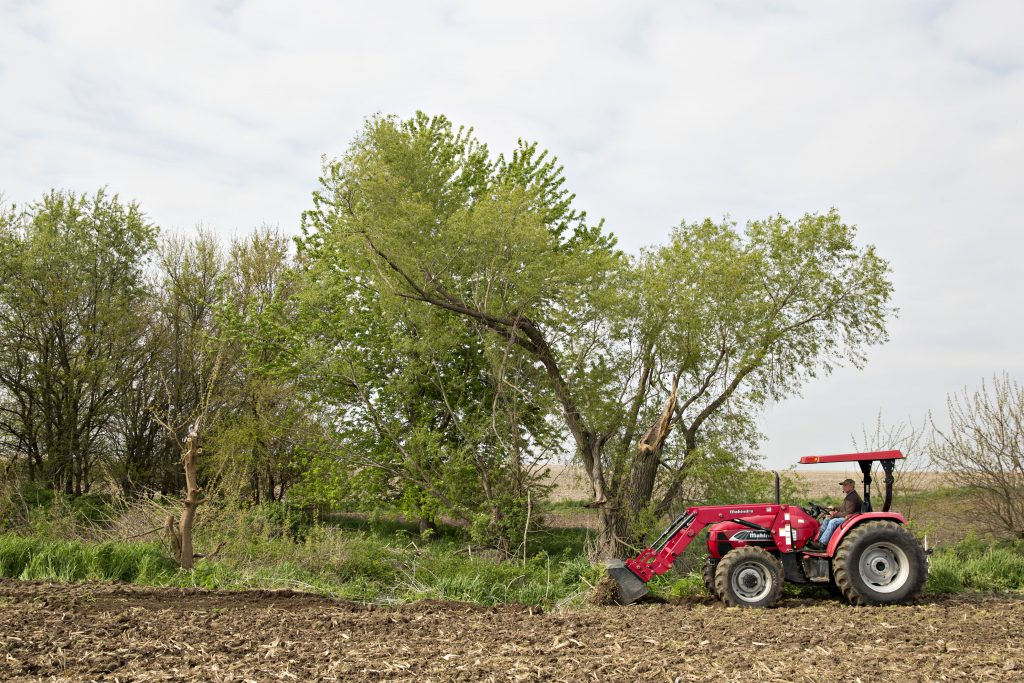 a red Mahindra tractor preparing a field for corn planting
