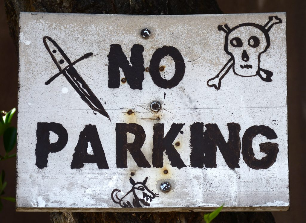 A 'No Parking' sign in Santa Fe, New Mexico, is embellished with threatening images including a skull-and-crossbones and a vicious dog.