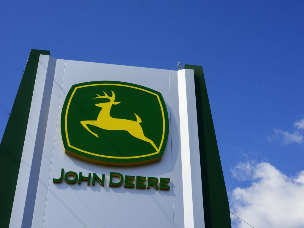a John Deere logo on a tall sign with blue cloudy skies