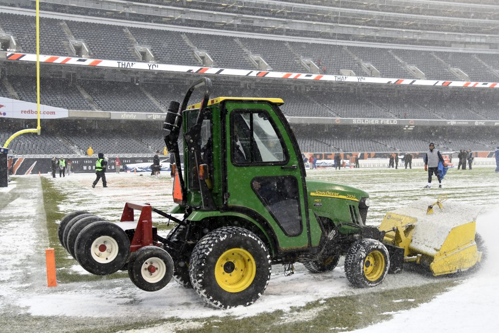a John deer compact tractor plowing snow on a football field.
