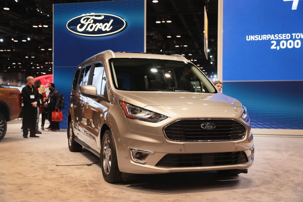 a silver ford transit connect at an auto show