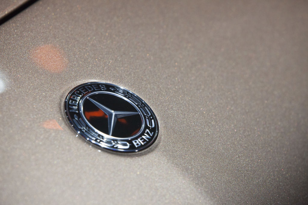 The Mercedes-Benz badge photographed on the nose of a car.