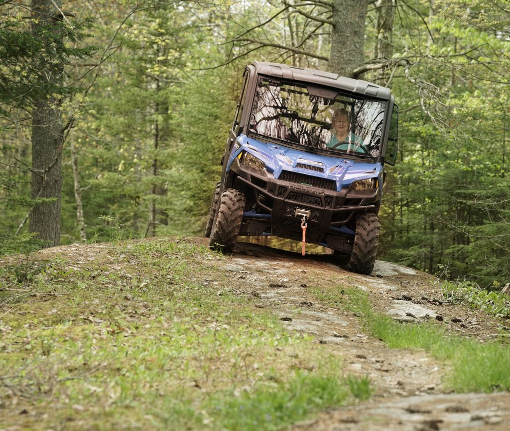 a blue Polaris Ranger in the forest
