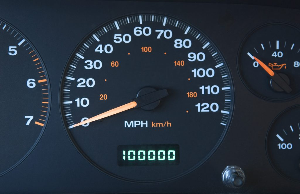 A high-mileage car shown with 100,000 miles on the odometer