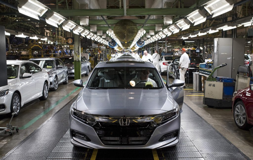 An employee prepares to drive a silver 2018 Honda Accord vehicle off the assembly line at the Honda of America Manufacturing Inc. Marysville Auto Plant
