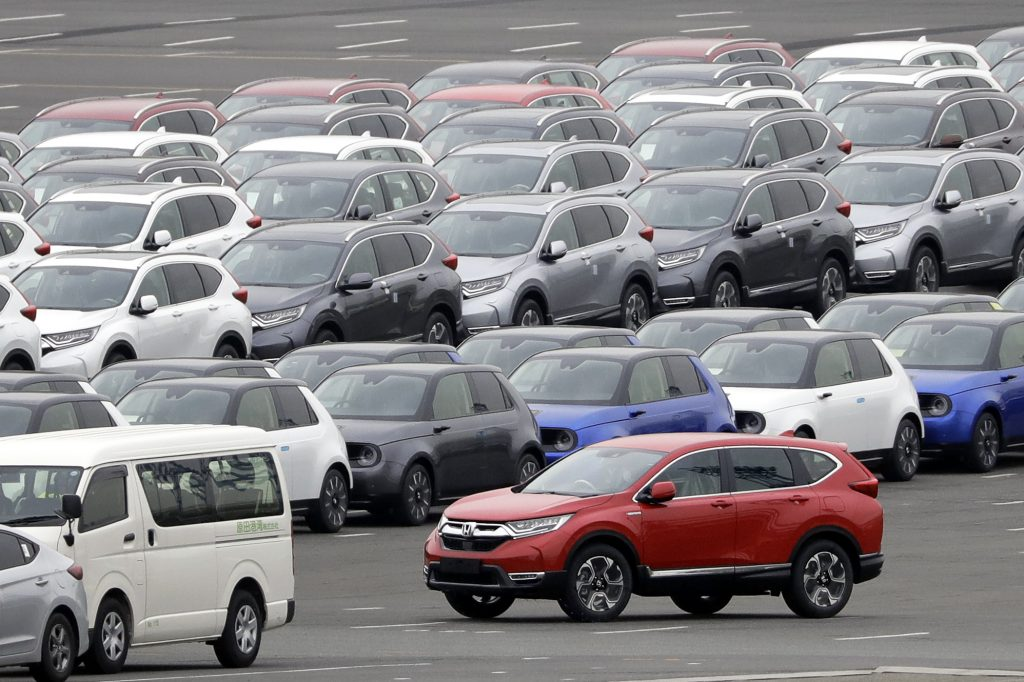 A red Honda Motor Co. CR-V sports utility vehicle (SUV) bound for shipment, bottom right, is driven while others sit parked at a port in Yokohama, Kanagawa Prefecture, Japan