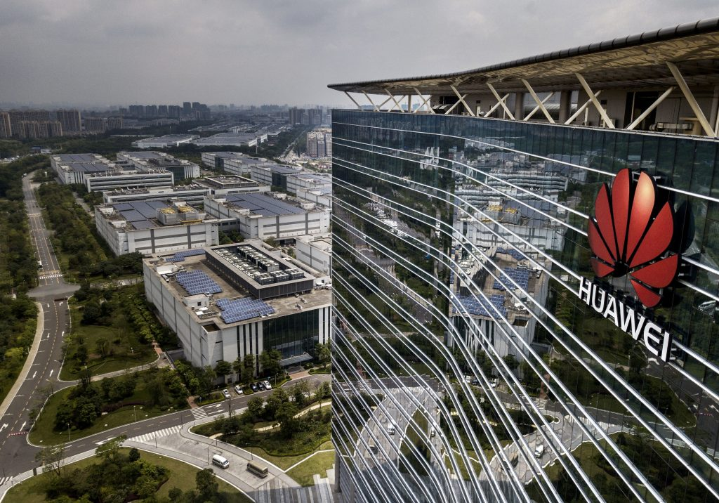The Huawei logo on the front of a tall production campus building