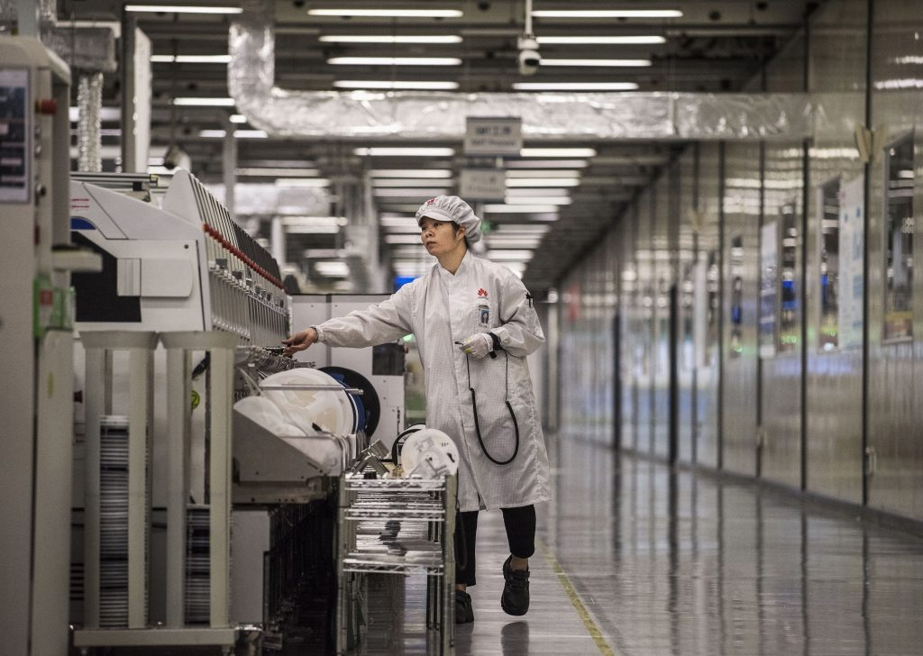 A woman packs up cellphones in a Huawei production plant