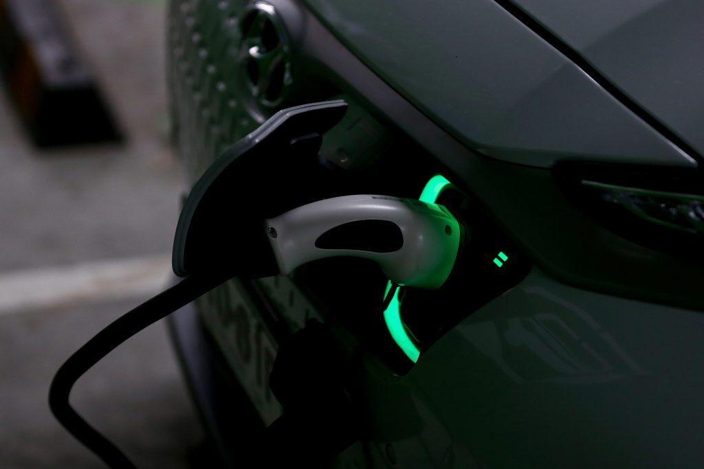White Hyundai Kona EV SUV charging in a dark garage. The charging plug is lit in green.