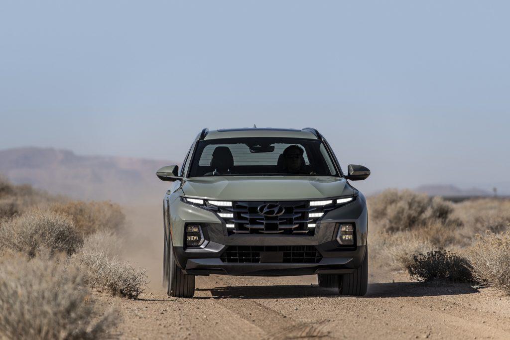 The gray 2022 Hyundai Santa Cruz driving in the desert.