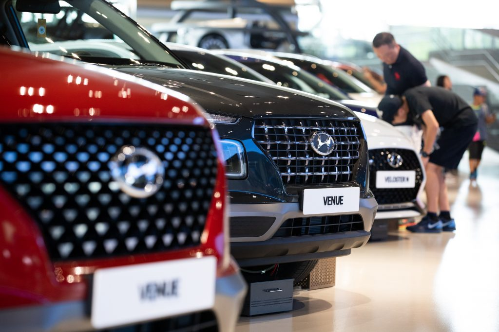 A red Hyundai Motor Co. Venue compact sport utility vehicle (SUV), center, stands on display at the company's Motorstudio showroom in Goyang, South Korea