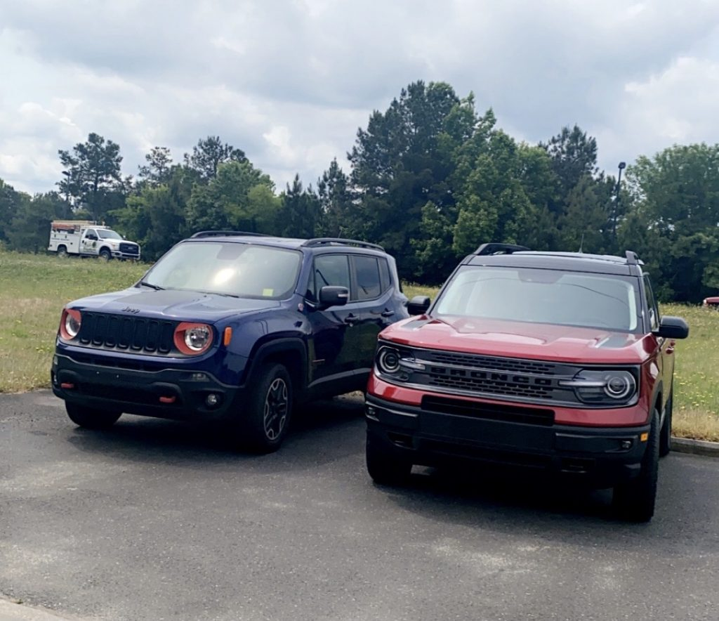 A blue 2016 Jeep Renegade Trailhawk model parked beside a red 2021 Ford Bronco Sport First Edition model