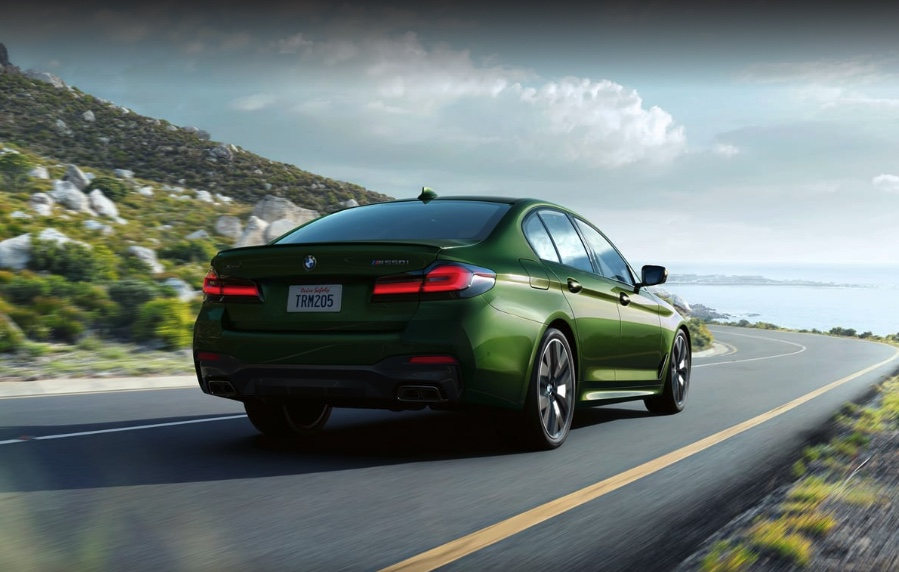 a bright green BMW 5 Series driving at speed on a scenic road near the sea
