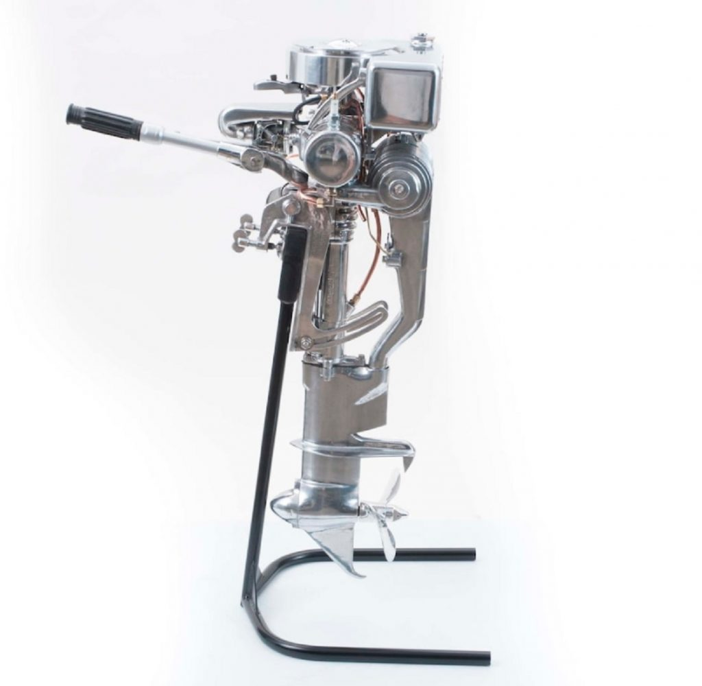 The side view of a silver Indian Silver Arrow outboard boat motor on its stand