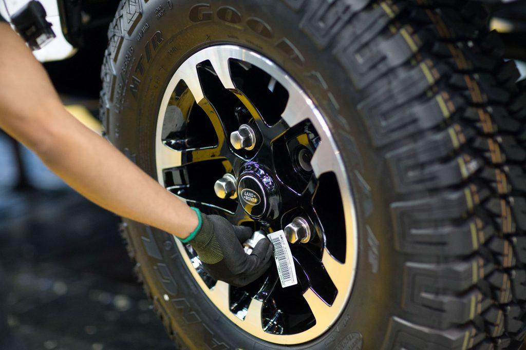 A JLR employee fits lug nuts on a 2015 Land Rover SUV