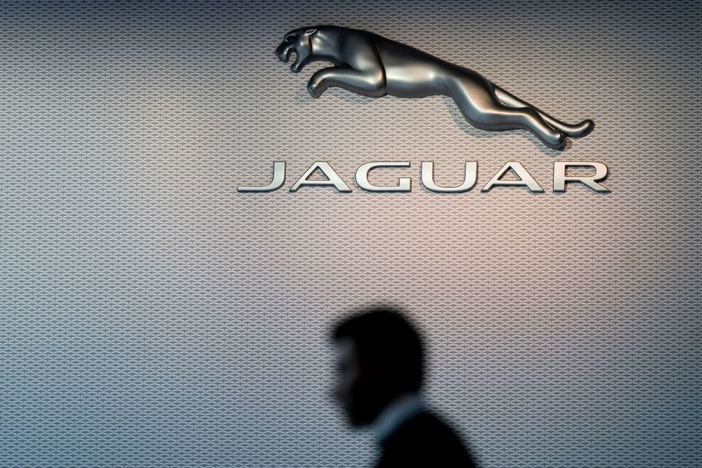 A man passes in front of Jaguar's leaping cat logo at the Brussels Motor Show