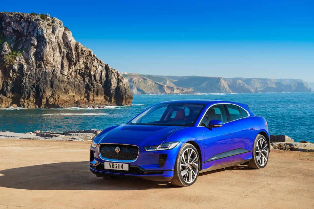 A blue Jaguar I-PACE parked by water