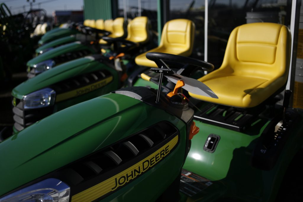 Pictured are John Deere riding lawn mowers. Before buying a lawn mower, consider the best lawn mower features.