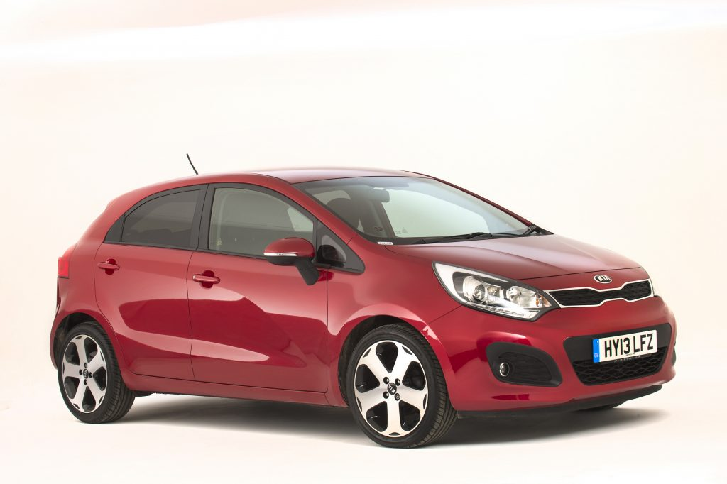 One of the smaller cars to make our list of most hated cars, the Kia Rio is featrured in cherry red, with an off-white backdrop.