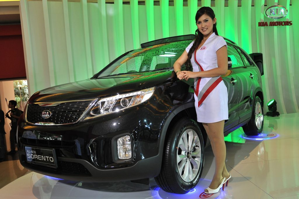 A model stands next to a black 2013 KIA Sorento on display at The 21st Indonesia International Motor Show