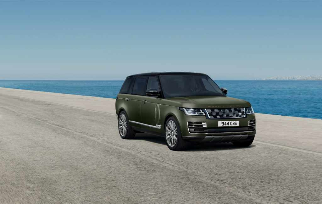 An army green Range Rover sits in the sun by the sea.